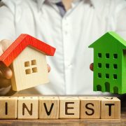 Wooden blocks shaped like houses, buildings, and the word INVEST