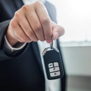 A sales agent present a key to a secondhand car
