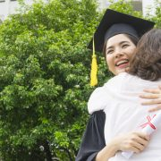 A newly graduated college student hugging her mother